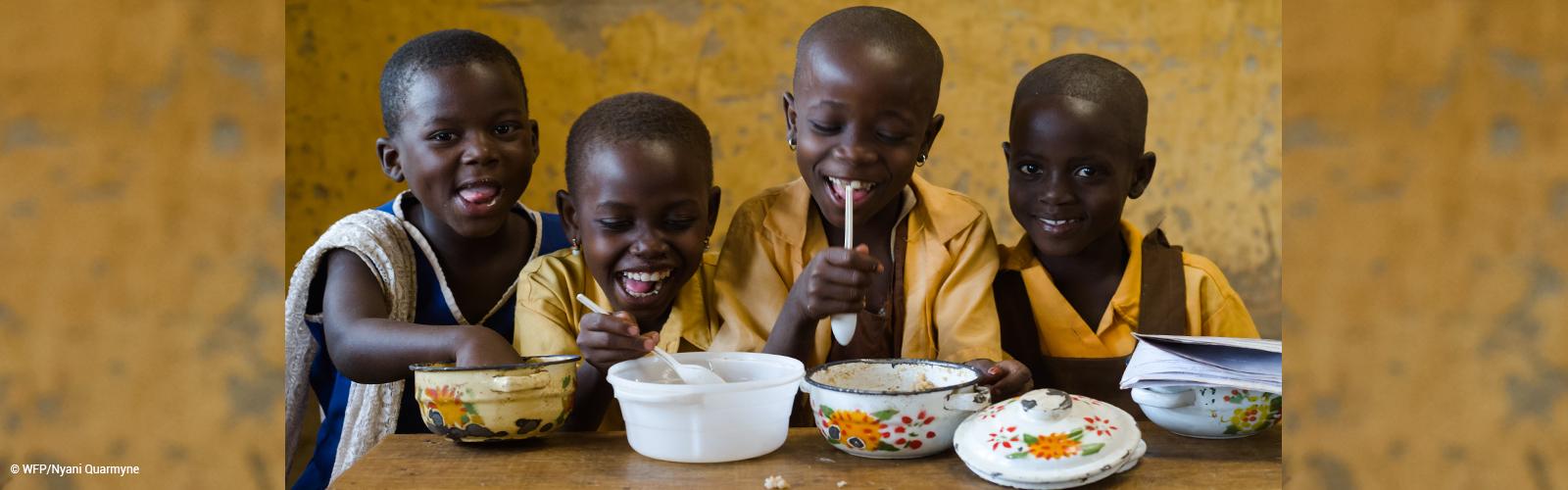 Quatro crianças estão em frente a uma mesa. Elas sorriem e comem em pratos com decoração de flores.