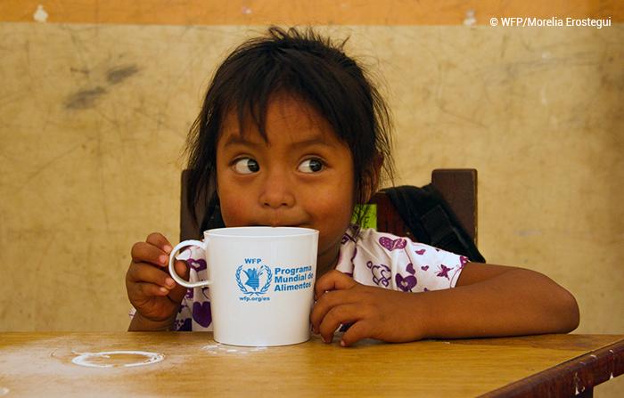"""Imagem mostra menina sentada à mesa, com uma caneca onde se lê """"Programa Mundial de Alimentos"""" em azul."""