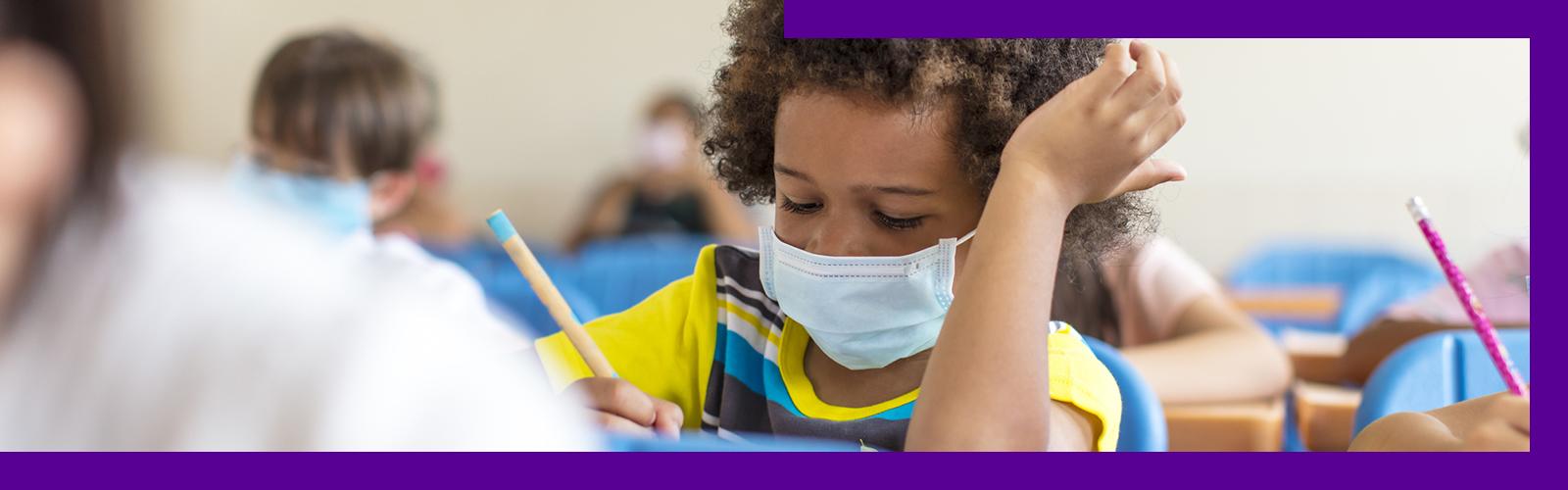 Imagem mostra uma criança sentada dentro da sala de aula de máscara, escrevendo.