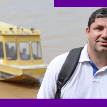 O Prof. Gilson da Silva, que atuou em escola atendida dentro do projeto Aula Digital, está sorrindo e, ao fundo, barcos se movimentam por rio que corta a cidade de Manaus (AM).