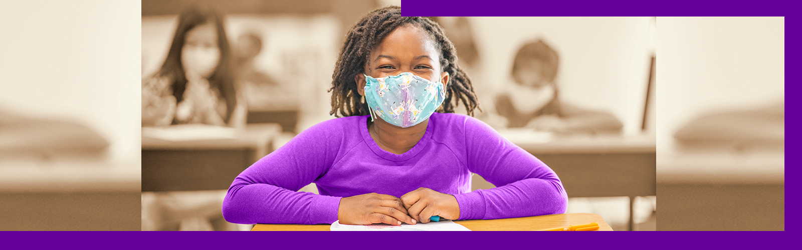 A imagem mostra uma crianca negra em destaque de máscara de proteção colorida e blusa de manga comprida cinza sentada em uma carteira escolar dentro de uma sala de aula. Ao fundo, é possível ver mais crianças sentadas, também de máscara.