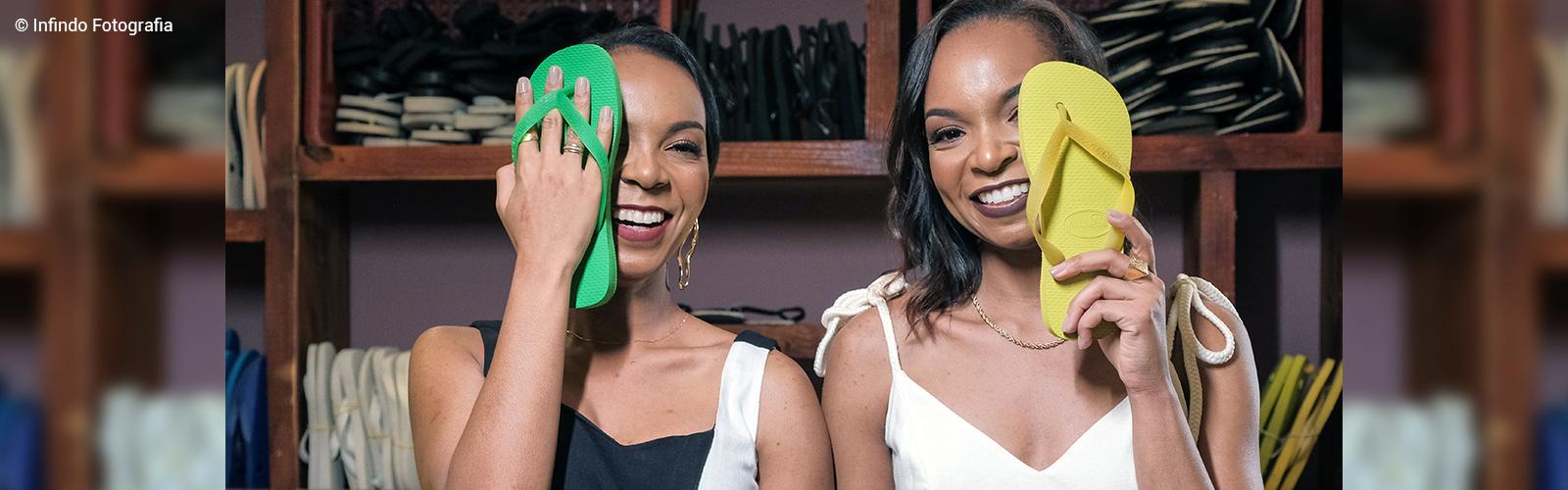 Betty e Brenda, fundadoras da ONG Compaixão Internacional, posam para foto segurando chinelos de dedo nas mãos, que escondem metade dos seus rostos