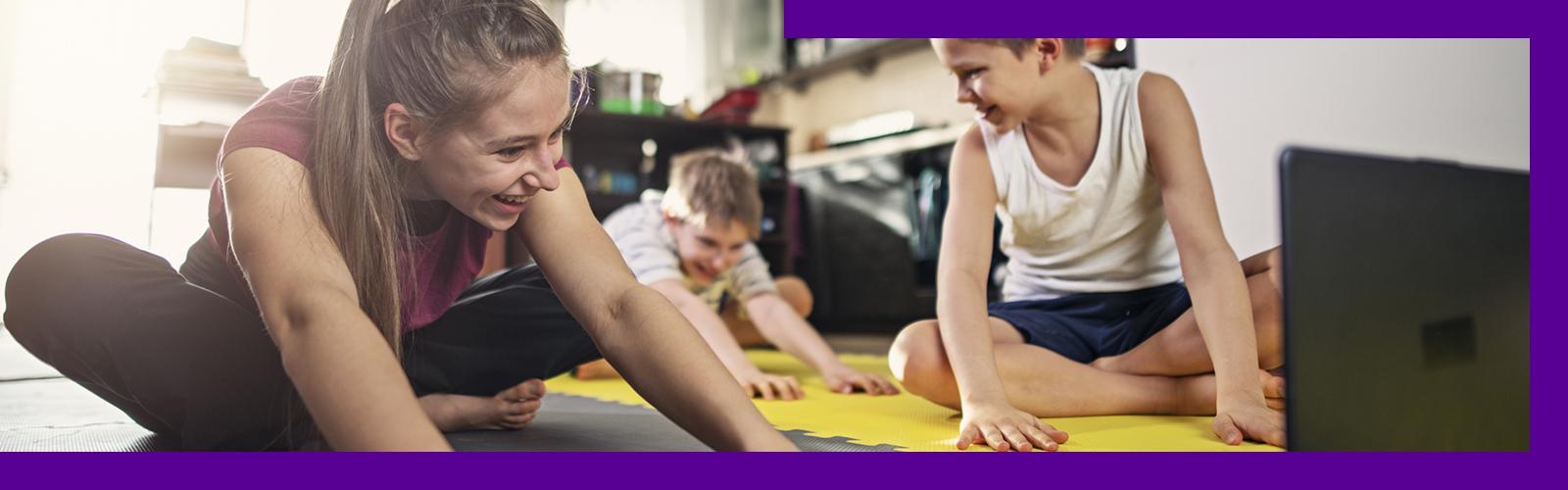 Imagem mostra mãe e filhos fazendo atividades físicas na sala de casa.