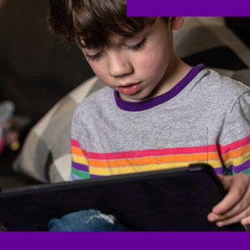 A imagem mostra um menino sentando no sofá, olhando para a tela de um tablet que está nas mãos dele.