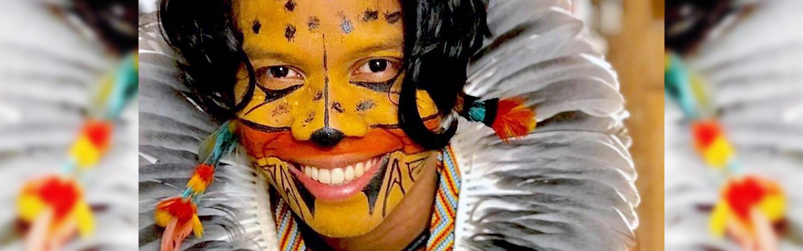 Tukumã Pataxó se destaca pelo ativismo indígena e aparece com pintura no rosto que se assemelha a uma onça, além de um cocar na cabeça, com penas em tons de cinza.
