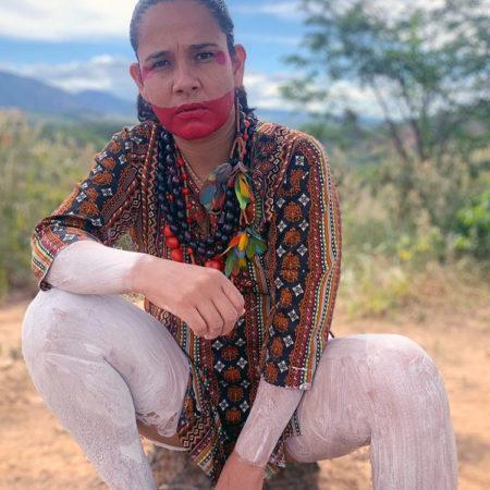 Shirley Djukurnã Krenak de destaca pelo ativismo indígena e aparece agachada, em meio a uma paisagem de cerrado, usando pintura tradicional, com parte do rosto pintado de vermelho e as pernas pintadas com tinta branca.