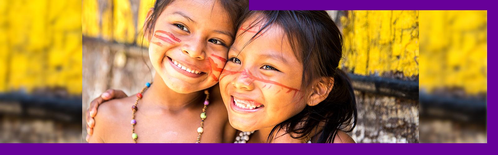 Imagem que ilustra pauta sobre literatura indígena mostra duas meninas abraçadas e sorrindo. Elas têm menos de 10 anos e trazem no rosto pinturas tradicionais de povos indígenas.