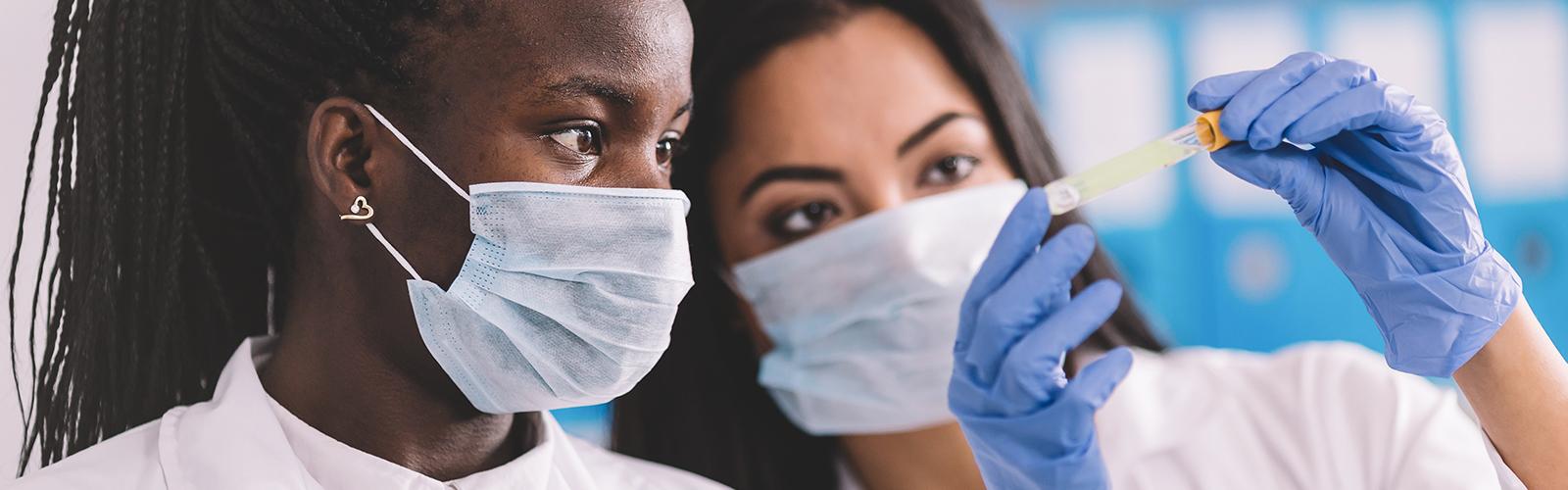 A imagem mostra duas jovens, uma negra e uma branca em um laboratório. Ambas estão com jaleco branco e máscara de proteção e uma delas segura um tubo de ensaio.