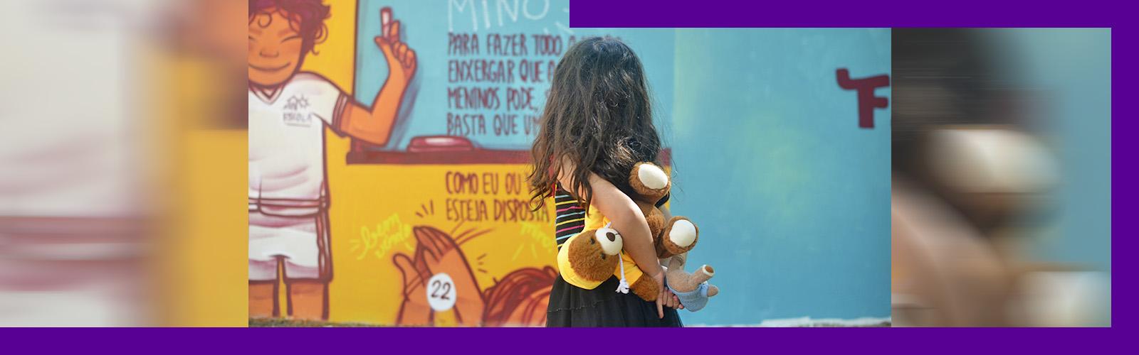 A imagem mostra uma criança de costas segurando um bicho de pelúcia olhando para o muro grafitado