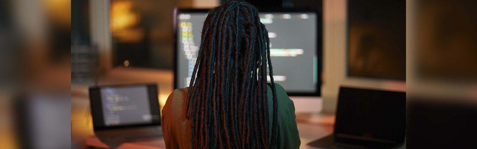 Mulher de dreads trabalha de costas. Na frente dela se vê um notebook e um computador.