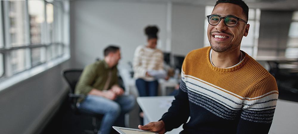 A imagem ilustra pauta sobre transição de carreira e mostra um ambiente de trabalho mais informal. Em primeiro plano há um homem jovem segurando um tablet e sorrindo para a foto. Ele é negro, usa óculos e barba, e está vestindo um suéter com listras nas cores ocre, branco, cinza e preto.