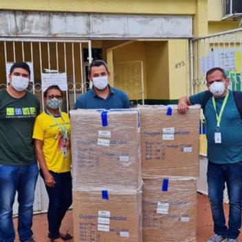 Imagem mostra um grupo usando máscaras de proteção e posando para a foto atrás de várias caixas de papelão com equipamentos médicos doados pela Fundação Telefônica Vivo em ação emergencial de apoio ao Amazonas
