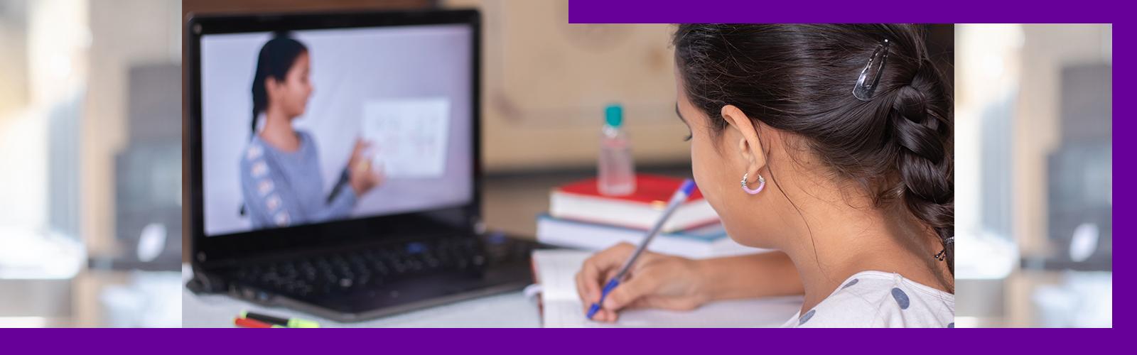 A imagem mostra uma criança de costas, olhando para a tela de um notebook onde se vê uma mulher segurando uma folha, enquanto faz anotações em um caderno