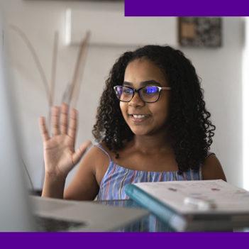 Imagem mostra uma menina sentada em frente a uma mesa onde está um notebook. Ela está sorrindo com uma das mãos levantadas.