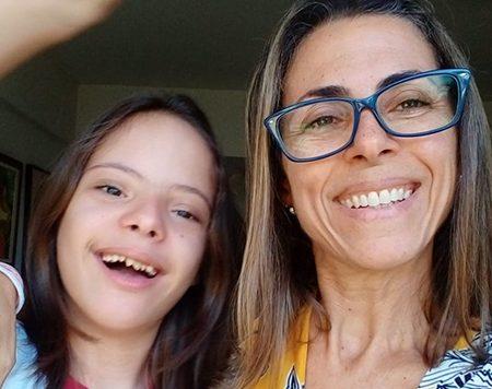 A educadora infantil Mônica Barreto e o filho Victor, que tem Síndrome de Down, posam para foto. Ambos estão abraçados, sorrindo para a foto.