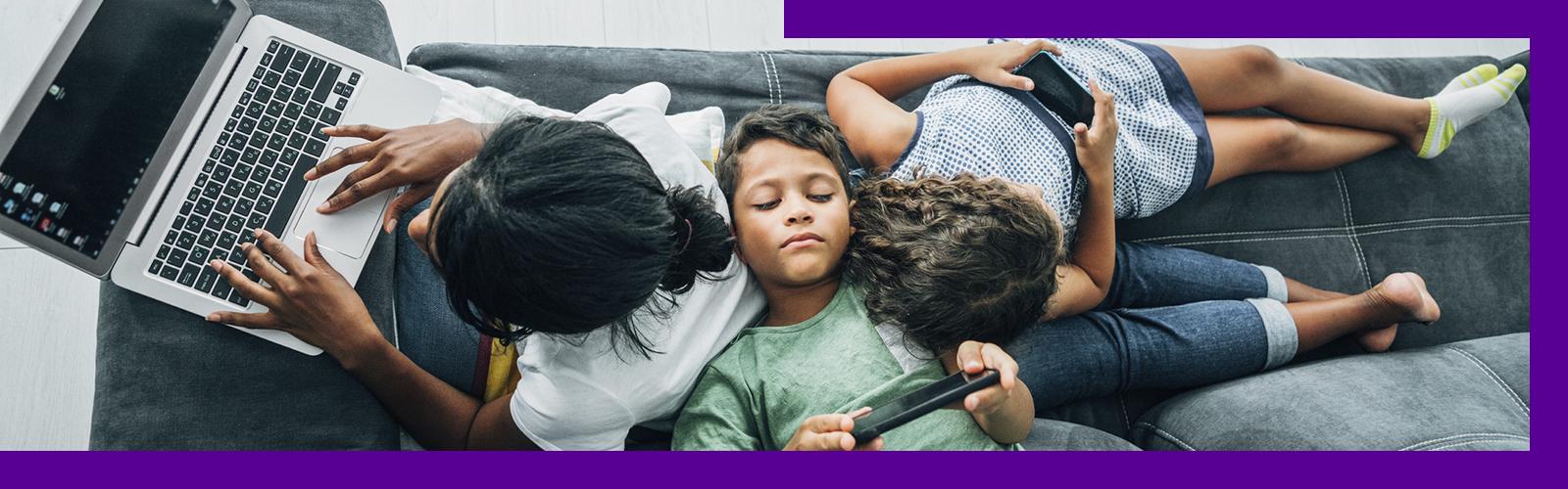 Imagem que ilustra o efeito do excesso de telas para crianças e adolescentes mostra três crianças apoiadas umas nas outras em um sofá. Uma delas usa um notebook , enquanto as outas duas estão olhando para as telas de smartphones.
