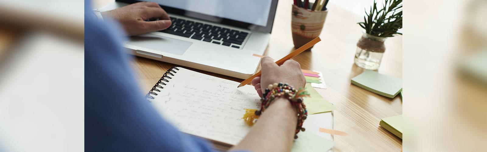 A imagem mostra as mãos de uma pessoa, em destaque, manuseando um notebook e escrevendo em um caderno sobre a mesa.