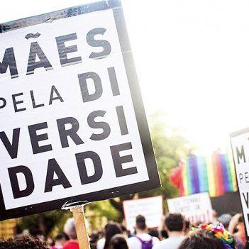 ONG Mães pela Diversidade atua no apoio a pais de filhos LGBTQIA+. Na imagem, cartaz traz o nome do coletivo em meio a uma passeata e a outros cartazes com as cores do arco íris.