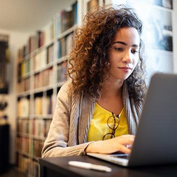 A imagem mostra uma jovem em uma sala mexendo em um notebook. Atrás dela, há uma estante grande repleta de livros.