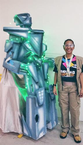 A professora Keila posa para foto ao lado de um robô construído com lixo eletrônico