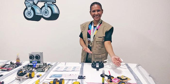 Professora Keila posa para foto atrás de uma mesa com diversos materiais utilizados em sua aula de robótica sustentável
