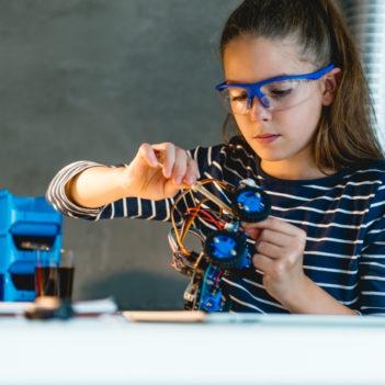 Menina está montando robô em uma bancada para representar pauta sobre a Coleção de Tecnologias Digitais. Ela usa óculos de proteção e tem os cabelos presos em rabo de cavalo.