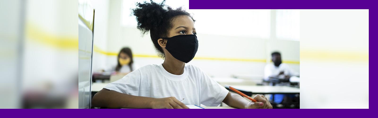 Imagem mostra uma menina dentro de uma sala de aula, sentada atrás de uma carteira escolar. Ela usa uma máscara de proteção preta, camiseta branca e segura um lápis na mão esquerda. Sobre a carteira há um caderno e um estojo.