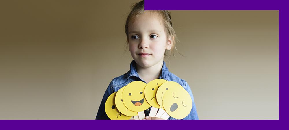 Em imagem que ilustra como ajudar as crianças a se expressarem, uma menina segura diversas placas que lembram emojis de expressões faciais, indicando sono, alegria, tristeza, entre outros. Ela está olhando para a frente com um sorriso discreto.