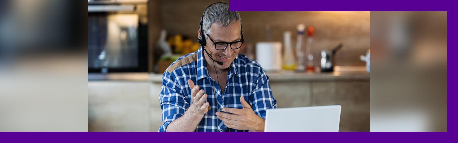 A imagem mostra um homem branco de meia idade, óculos de grau, vestido uma camisa xadrez azul e branca. Ele está sentado em frente a um computador, com um headfone, sorrindo enquanto gesticula.