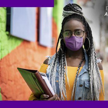 Imagem de uma jovem andando pela rua, carregando alguns cadernos. Ela é negra, com tranças coloridas e óculos de grau, e usa uma máscara de proteção e brincos de argola. Ao lado superior direito, há a frase Educar é Acreditar e o ícone de um livro.