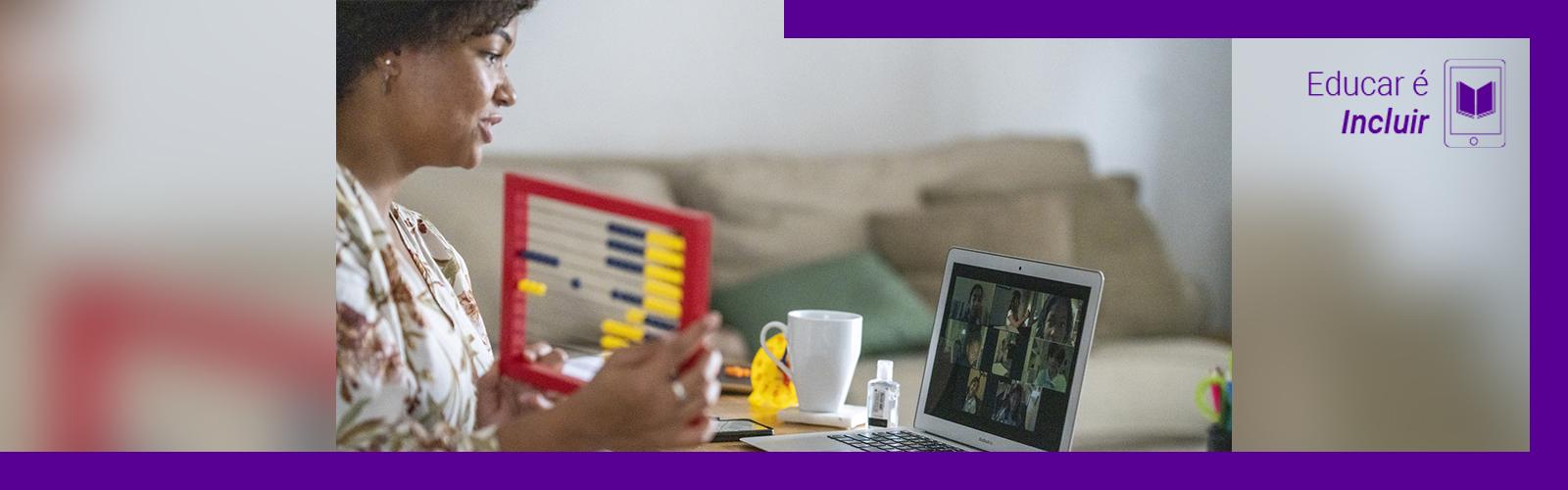 A imagem mostra uma mulher na sala de sua casa, sentada em frente a uma mesa onde está um computador, um ábaco e uma xícara de porcelana. Ela está olhando para tela e interagindo com um grupo de pessoas em uma videoconferência