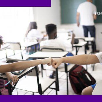 A imagem mostra duas crianças dentro de uma sala de aula, usando máscaras de proteção, se cumprimentando com as palmas das mãos fechadas.