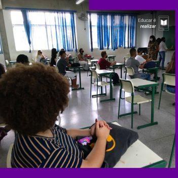 A pauta Educar é realizar traz a imagem de uma sala de aula em que um grupo de aproximadamente dez pessoas estão sentadas em carteiras olhando para três educadoras que estão afrente da sala, próximas à lousa.