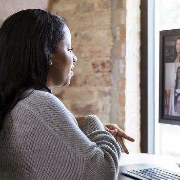 A imagem mostra uma mulher negra de costas, de longos cabelos castanho escuro. Ela está sentada, olhando para a tela de um computador, onde aparece a imagem de várias pessoas em uma videoconferência.