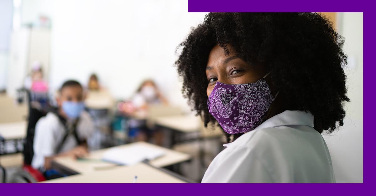 Imagem de uma professora negra em destaque dentro de uma sala de aula. Ela usa máscaras de proteção e os alunos sentados ao fundo também.