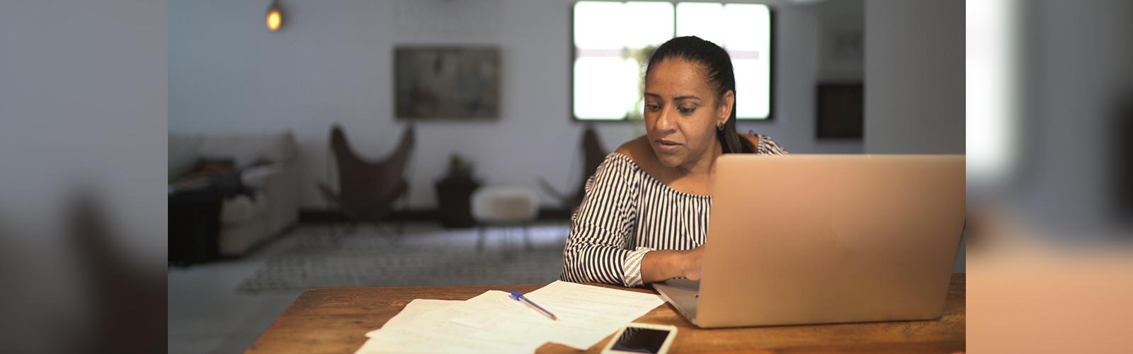 Mulher na sala de uma casa, sentada em frente a um computador, olhando para uns papeis sobre a mesa.
