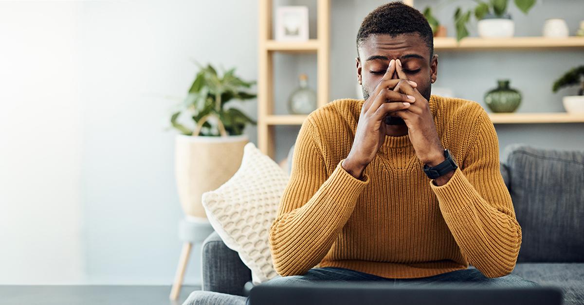 Imagem mostra um jovem na sala de casa, pensativo com as mãos sobre o rosto e o olhos fechados.