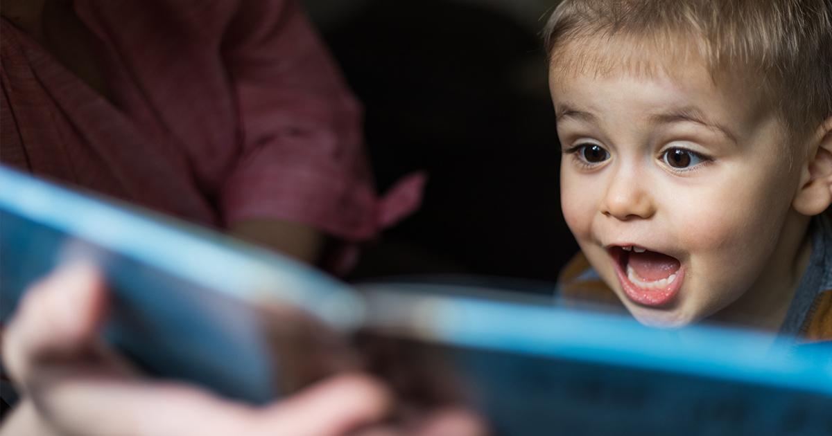 Imagem destaca o rosto de um menino de cabelos loiros, olhando de boca aberta e expressão de surpresa para as páginas de um livro aberto