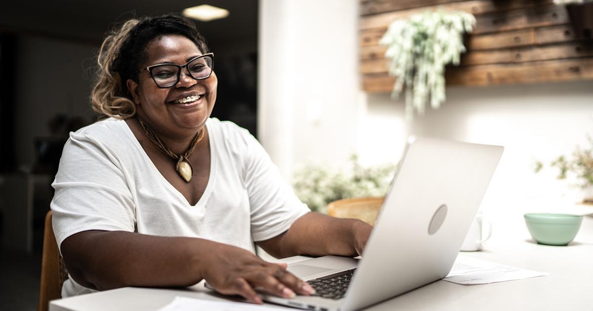 Imagem mostra uma mulher negra, de camiseta branca e um colar. Ela está sentada em frente um computador, sorrindo enquanto olha para a tela.