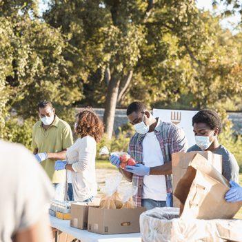 A imagem mostra um grupo de pessoas em um ambiente aberto, ao ar livre, manuseando mantimentos e caixas de doações. Todas estão usando máscara de proteção individual e luvas.
