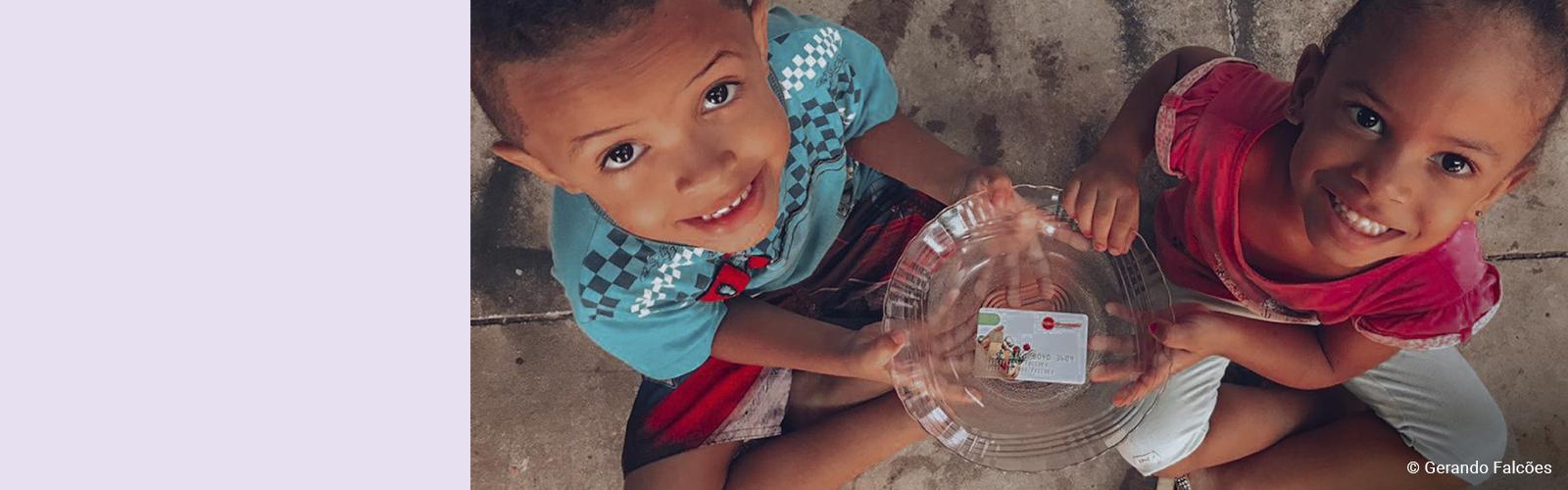Imagem de duas crianças sentadas no chão, sorrindo e olhando para cima enquanto seguram um prato de vidro com um cartão de alimentação dentro dele.
