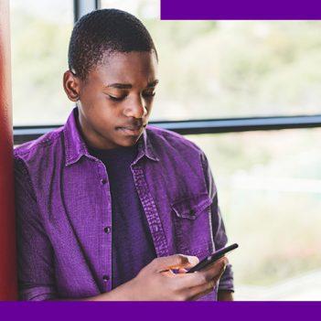 Imagem de um jovem negro, de camisa púrpura, encostado na parede, olhando para a tela de um celular que está nas mãos dele