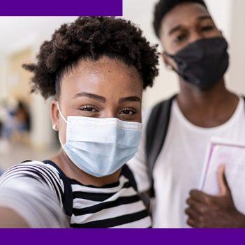 Imagem mostra em destaque dois estudantes jovens no corredor da escola, usando máscara de proteção individual