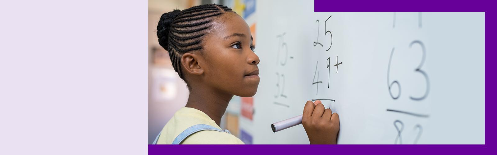 Imagem mostra uma estudante resolvendo uma conta matemática em um quadro branco
