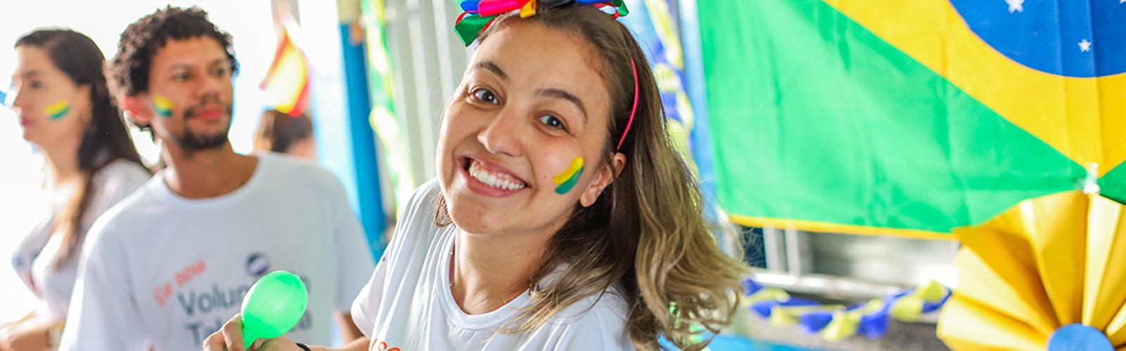 Imagem de uma voluntária com o rosto pintado e a bandeira do Brasil ao fundo, durante o programa Vacaciones Solidárias