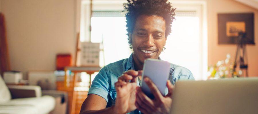 Imagem de um jovem na sala de sua casa, sorrindo enquanto mexe no celular