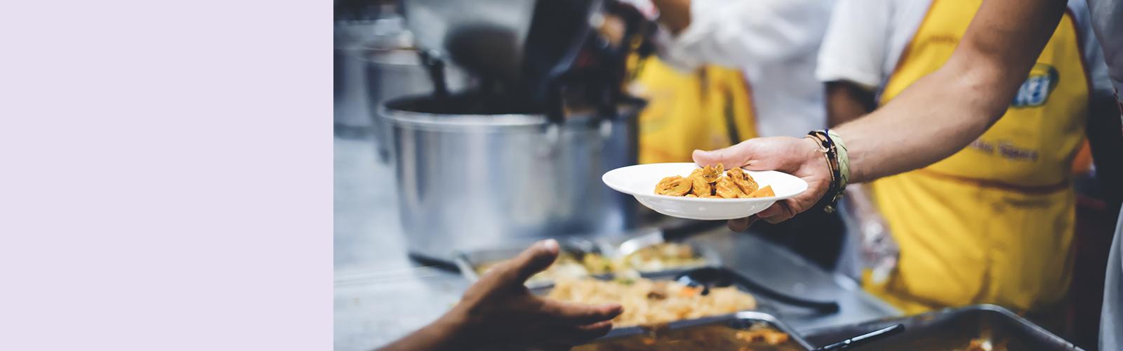 Imagem de uma pessoa entregando um prato de comida para outra pessoa.