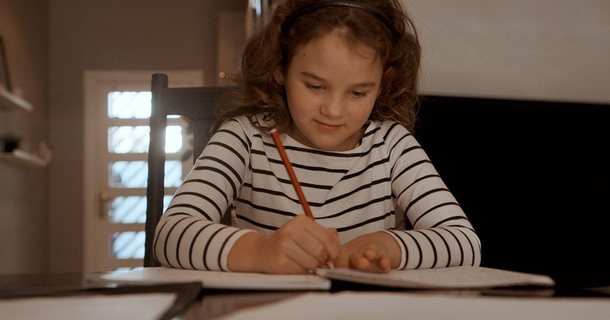 Imagem de uma menina escrevendo em folhas de papel.