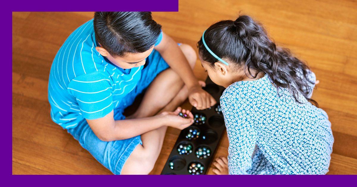 Duas crianças brincam de Mancala no chão