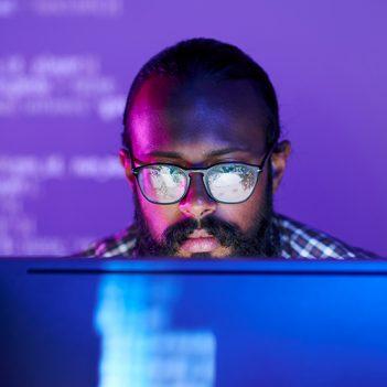 Imagem de um homem de óculos olhando para o computador.